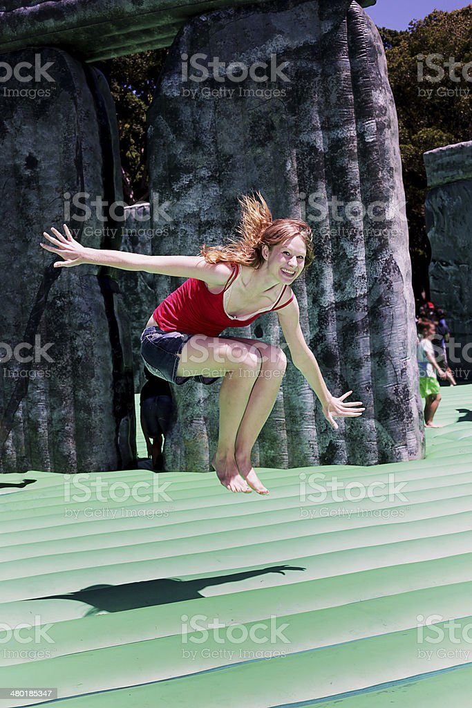 Happy redhead woman enjoying a bouncy castle stock photo