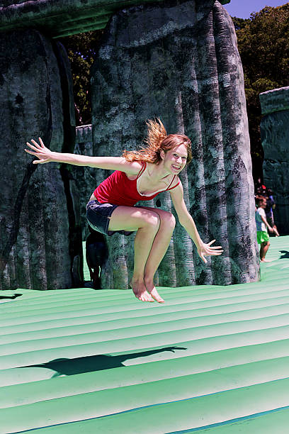 Happy redhead woman enjoying a bouncy castle stock photo