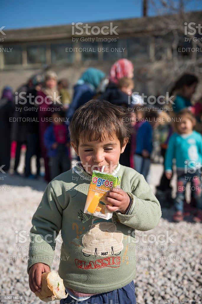 Happy refugee boy with orange juice and sandwich stock photo