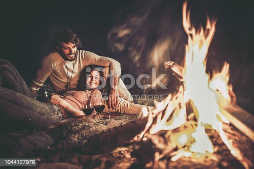 Young happy couple relaxing on the beach by the campfire at night.