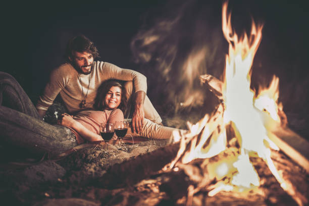 happy relaxed couple enjoying in their date night by the campfire. - falò spiaggia foto e immagini stock