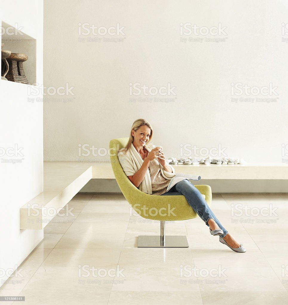 Happy relaxed female drinking coffee in an empty modern room royalty-free stock photo