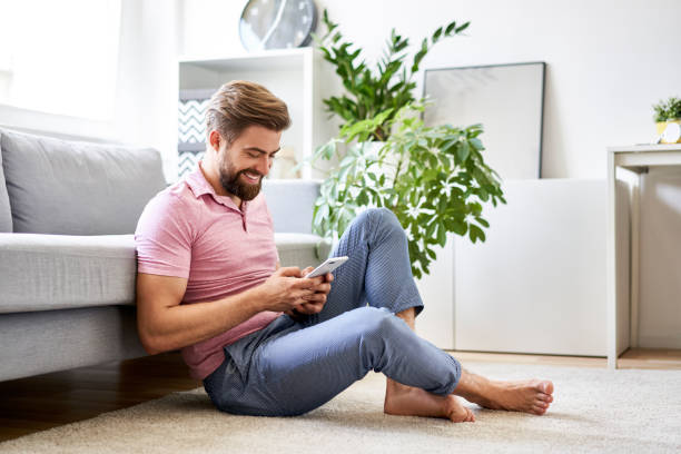 Happy, relaxed man at home using phone sitting on the floor stock photo