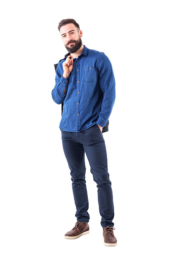 931173966 istock photo Happy relaxed smiling man in blue denim shirt carrying jacket over shoulder looking at camera 931173274