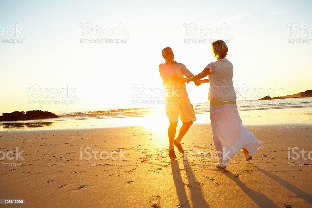 Happy retired couple enjoying together on beach royalty-free stock photo
