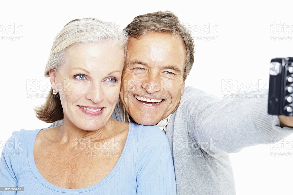 Happy retired couple taking self portrait against white royalty-free stock photo