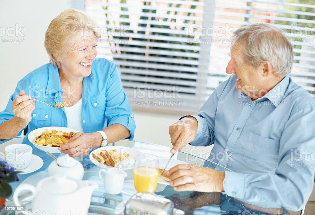 Happy retired senior couple enjoying breakfast royalty-free stock photo