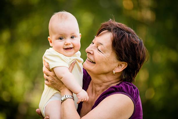 Happy retirement - grandmother with baby stock photo