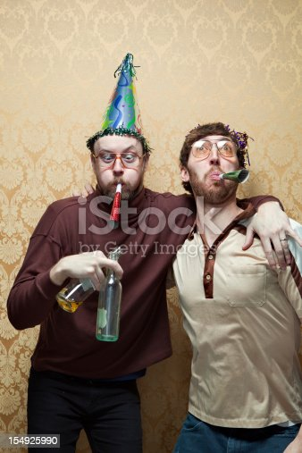 Two men in 70's style clothing and big party hats stand in front of a vintage damask wallpaper background, celebrating what could be a birthday party or New Years eve.  Both men blow party horns and make goofy faces, one holding two empty bottles of beer.