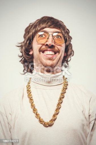 A shaggy 1970's man with stereotypical hair, glasses, giant gold chain and mustache, smiles with a proud facial expression.  Vintage emulation processing, edited to have a film