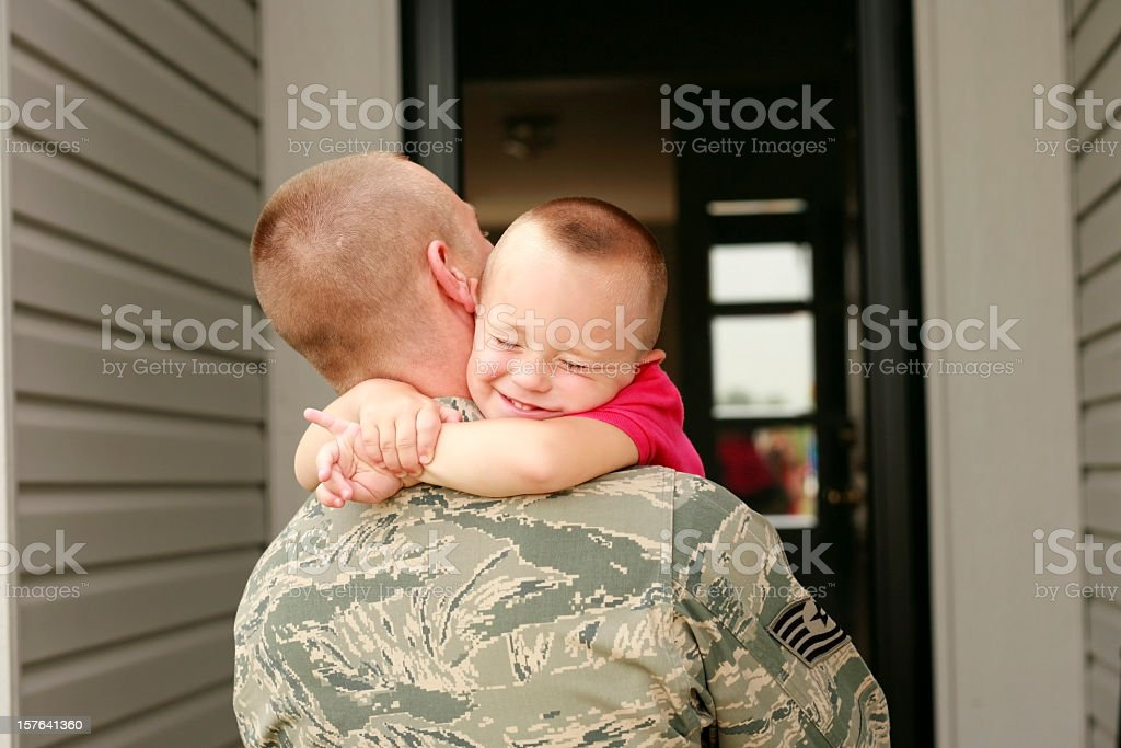 Happy return of military father holding his son stock photo