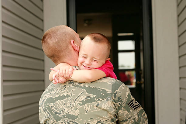 Happy return of military father holding his son Military dad hugging his son tightly. air force stock pictures, royalty-free photos & images
