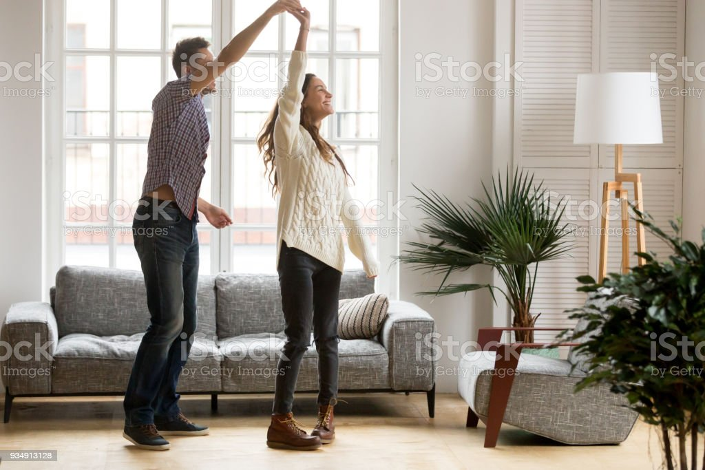 Happy romantic couple dancing in living room at home together stock photo