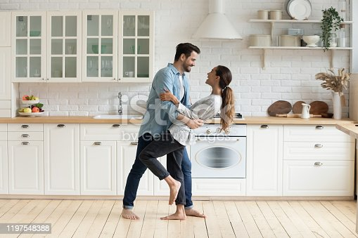 Happy romantic young couple bonding dancing in modern kitchen with white furniture enjoy sweet moments of affection, cheerful husband and wife celebrating anniversary having fun at home lifestyle