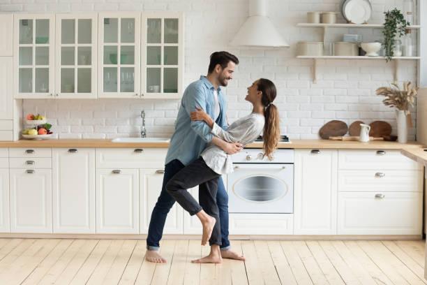 dança romântica feliz dos pares na cozinha moderna em casa - dançar - fotografias e filmes do acervo