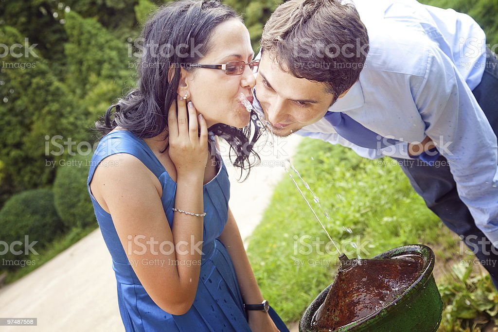 Happy romantic couple drinking water from park fountain royalty-free stock photo