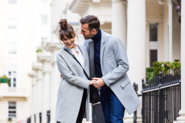 Happy romantic couple flirting in the city street stock photo