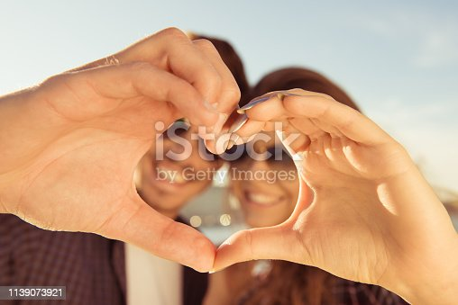 950598260 istock photo Happy romantic couple in love gesturing a heart with fingers 1139073921