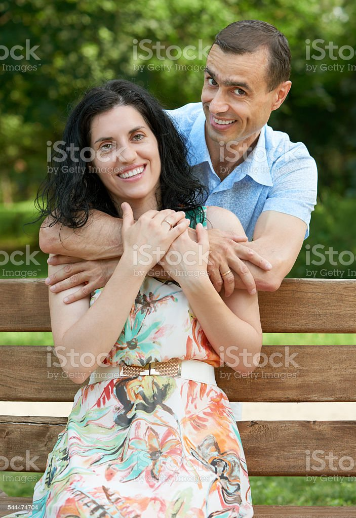 Happy Romantic Couple Sit On Bench In Park And Posing Royalty Free Stock Photo