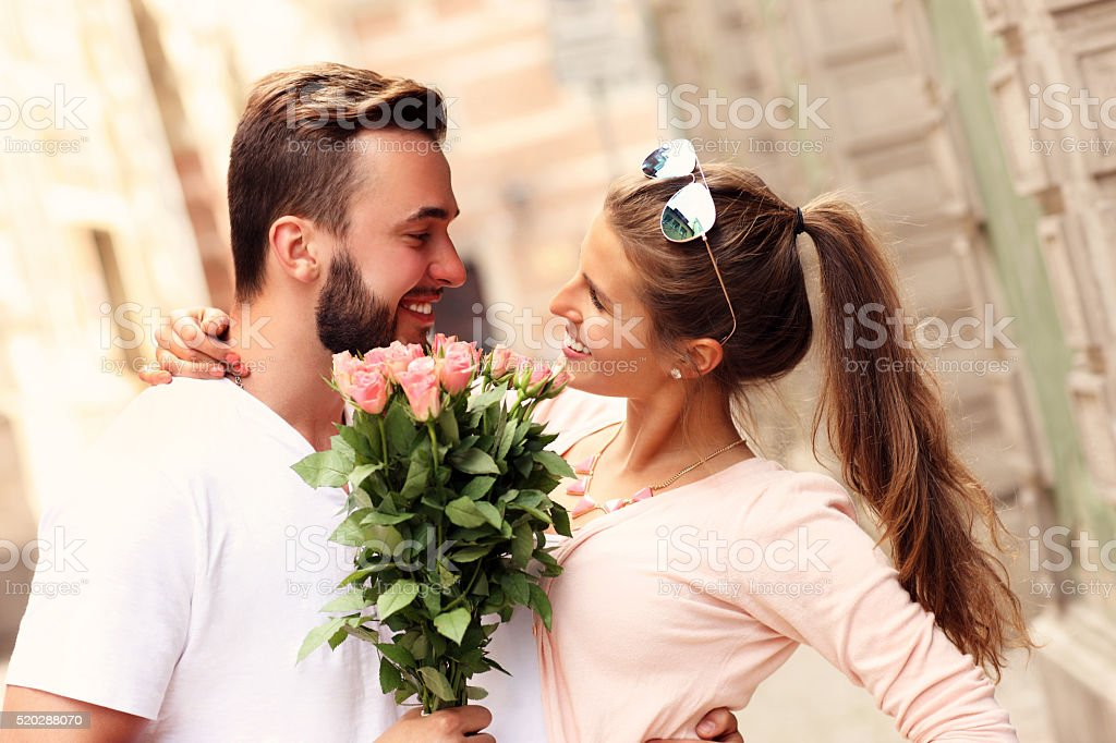 Happy romantic couple with flowers stock photo