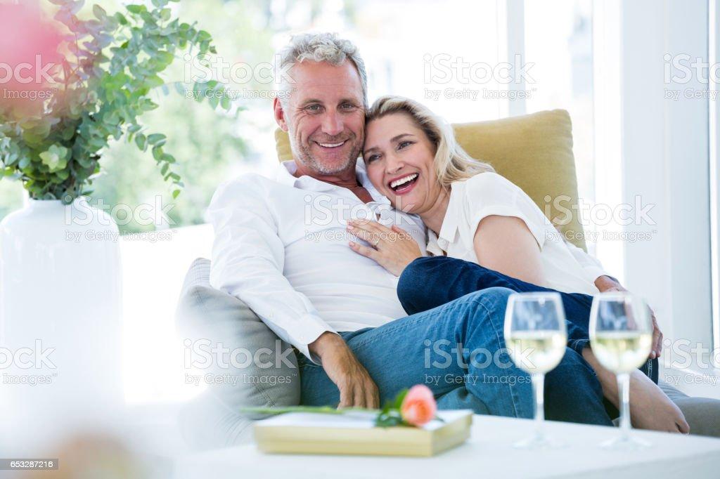 Happy romantic mature couple sitting on armchair stock photo