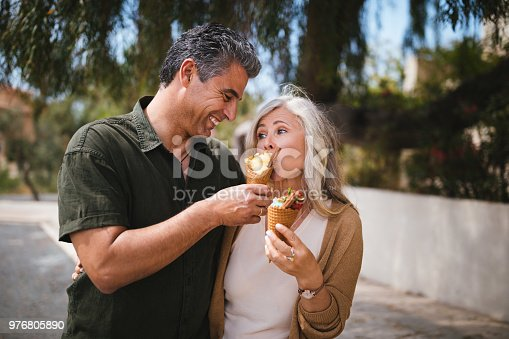 510491454 istock photo Happy romantic multi-ethnic senior couple eating ice cream in summer 976805890