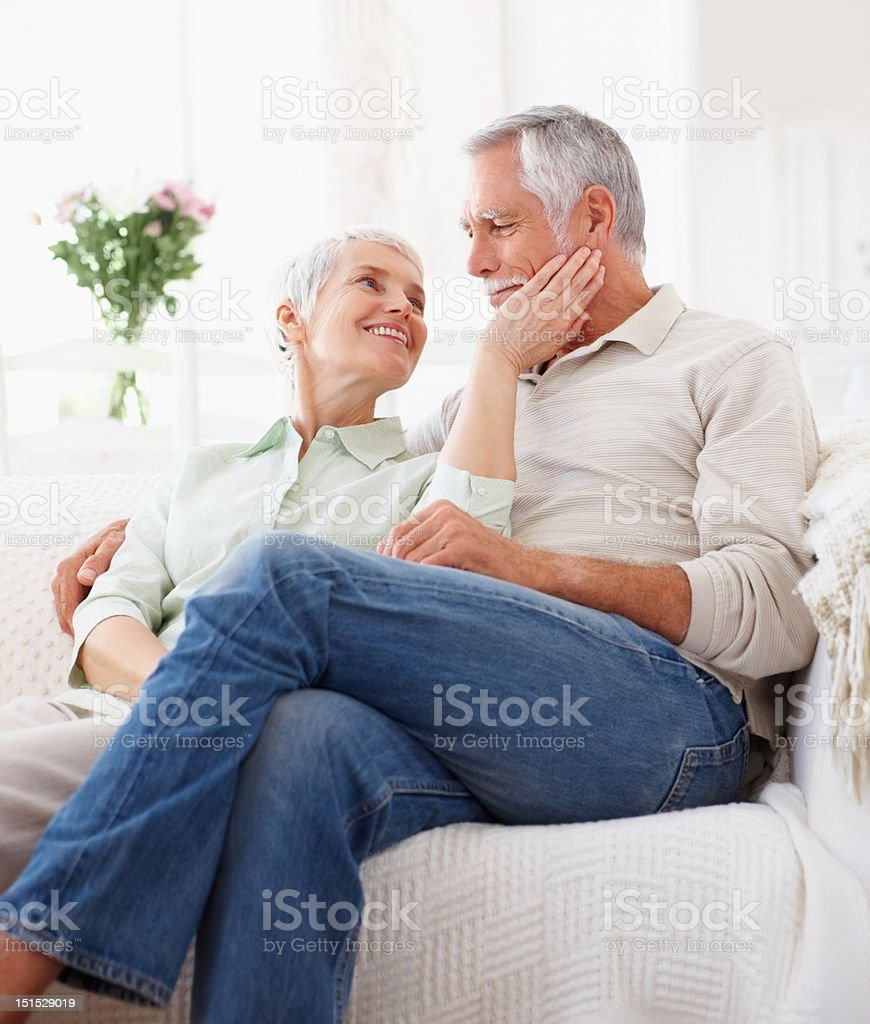 Happy romantic senior couple sitting on couch royalty-free stock photo