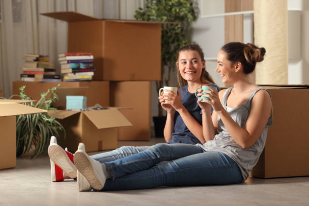 Happy roommates moving home resting and talking stock photo