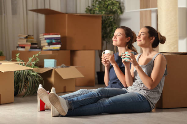 Happy roommates moving home resting breathing fresh air stock photo