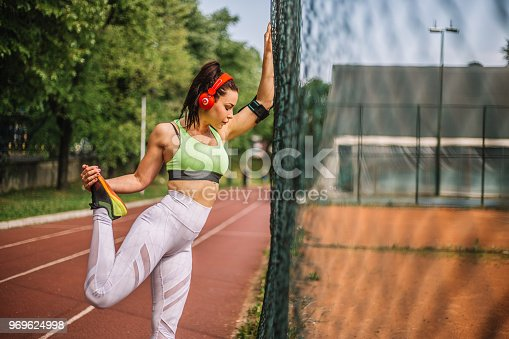 520047182istockphoto Happy runner woman doing stretching exercises 969624998