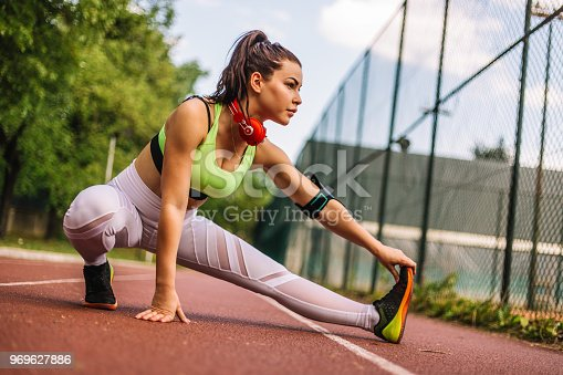520047182istockphoto Happy runner woman doing stretching exercises 969627886