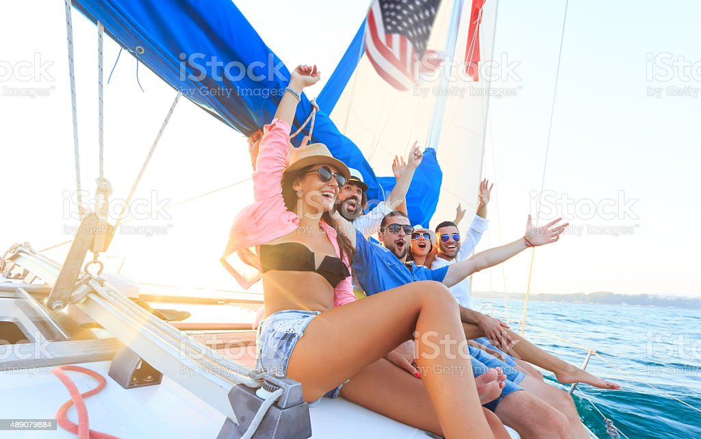 Happy sailing crew on sailboat stock photo