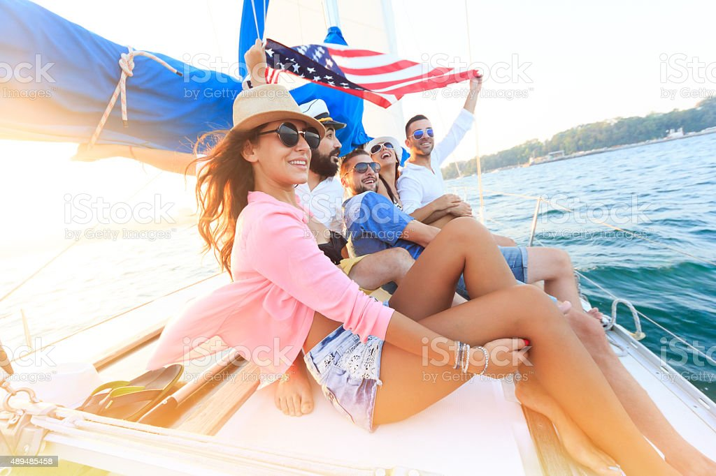 Happy sailing crew on sailboat with american flag stock photo