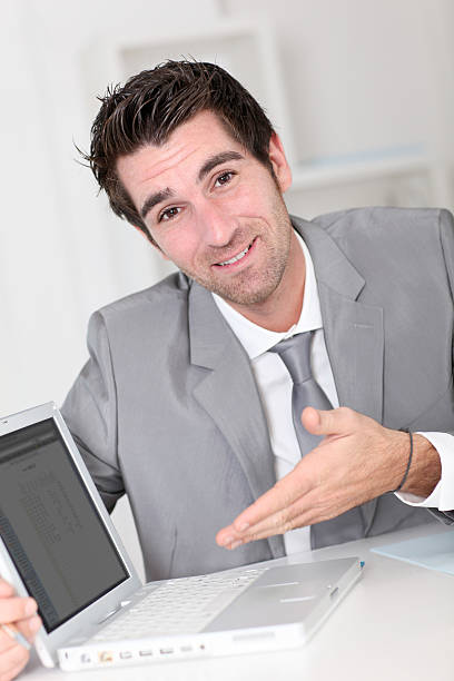 Happy salesman in office showing screen of tablet stock photo
