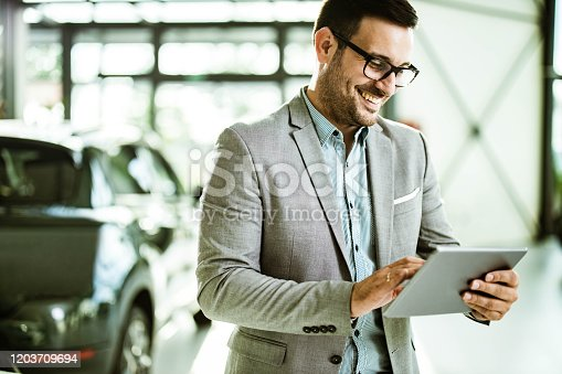 Young happy car salesperson reading an e-mail on digital tablet in showroom.