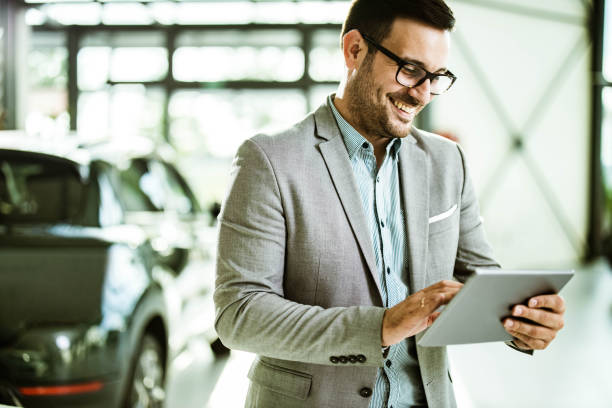Happy salesman with digital tablet in car showroom. stock photo