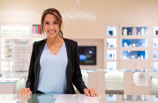 Happy saleswoman working at a jewelry store Portrait of a happy saleswoman working at a jewelry store and looking at the camera smiling jeweller stock pictures, royalty-free photos & images
