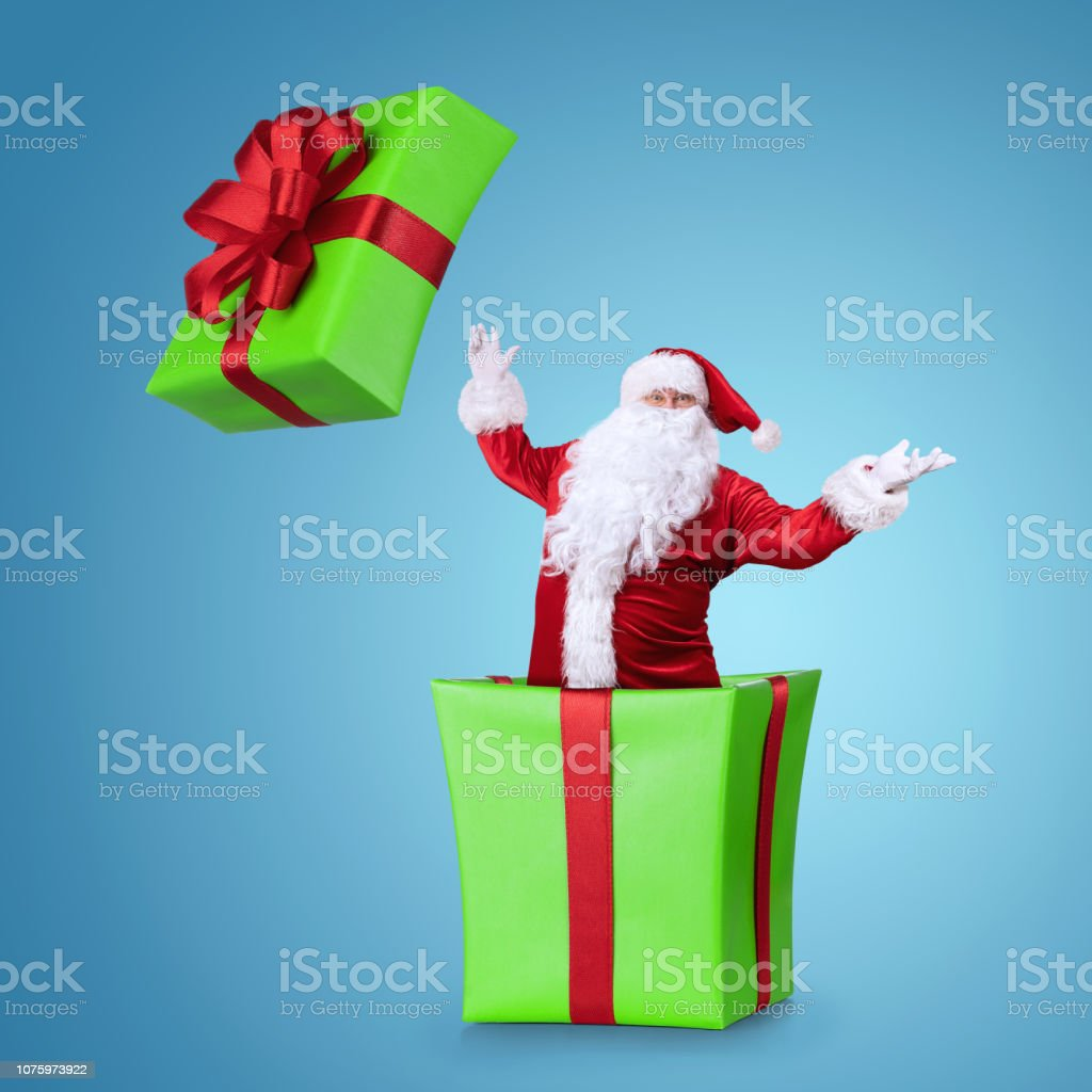 Happy Samta Claus jumping out of the christmas box isolated on blue...