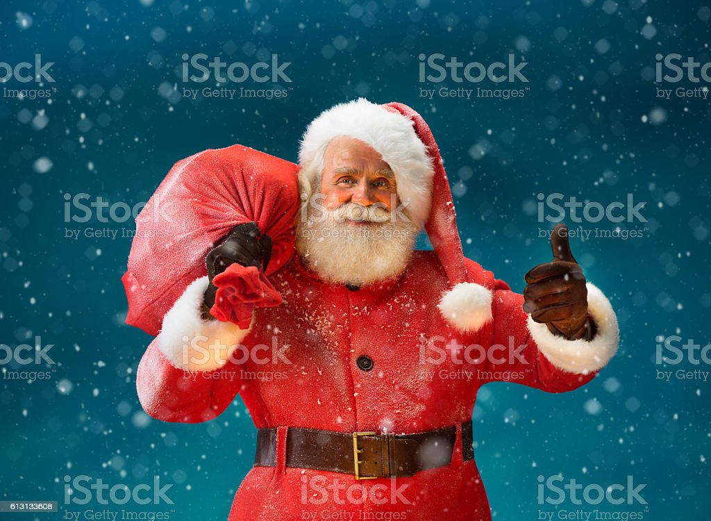 Happy Santa Claus gesturing thumb up with big bag stock photo