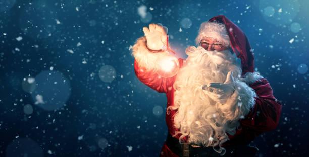 glücklicher weihnachtsmann hält glühende weihnachtskugel über defokussierten blauen hintergrund - santa stock-fotos und bilder