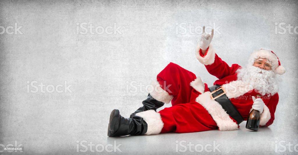 Feliz Papai Noel deitado no chão com uma garrafa de vinho foto de stock royalty-free
