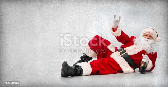 istock Happy Santa Claus lying on the floor with a bottle of wine 876564306