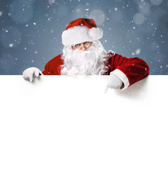 Happy Santa Claus pointing in blank white advertisement banner stock photo
