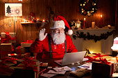 istock Happy Santa Claus waving hand video calling kid talking to child greeting on Merry Christmas, Happy New Year in virtual video online chat on laptop sitting at home table late with present on xmas eve. 1280356987
