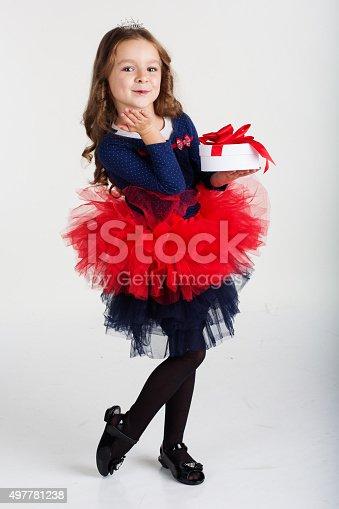 1061876006istockphoto Happy santa girl is holding gift box, christmas time 497781238