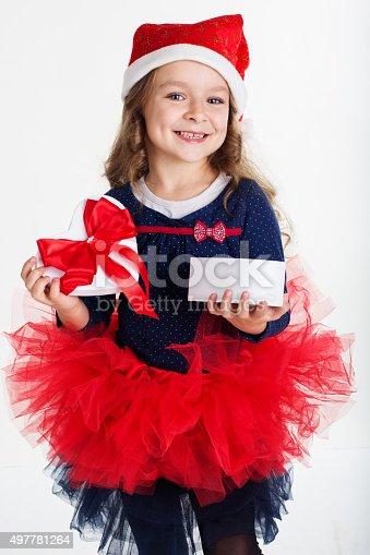 1061876006istockphoto Happy santa girl is holding gift box 497781264