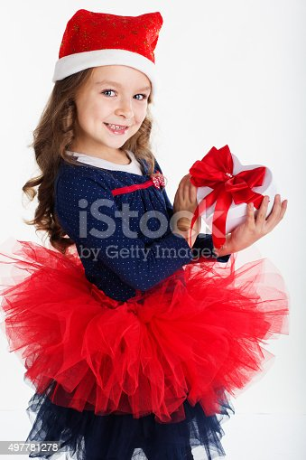 1061876006istockphoto Happy santa girl is holding gift box with red ribbon 497781278