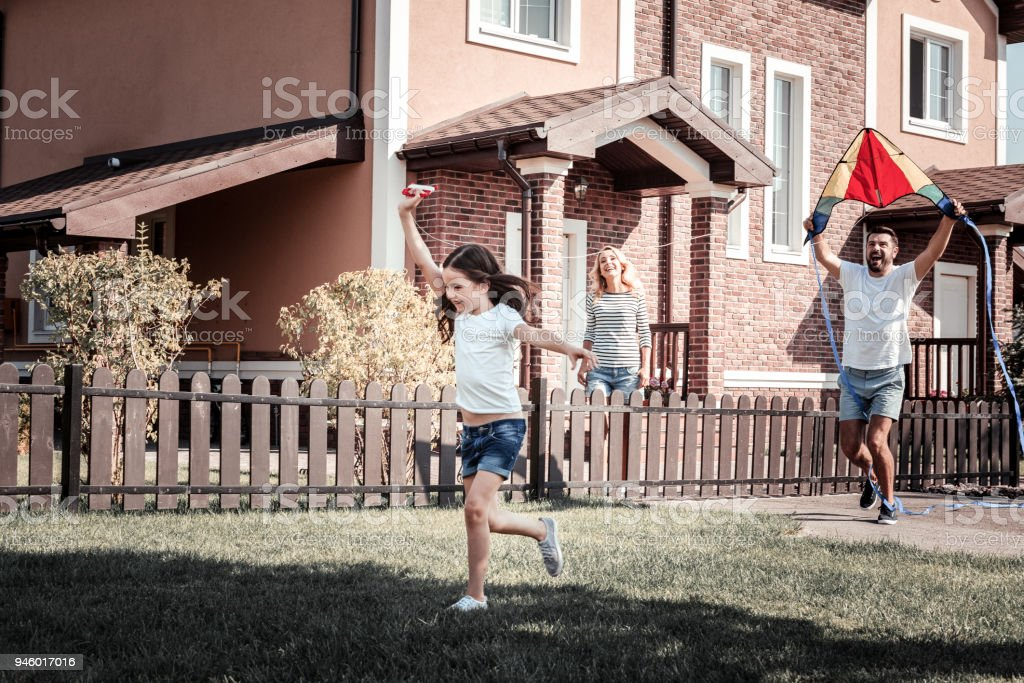 Happy satisfied father helping his daughter playing with her. stock photo