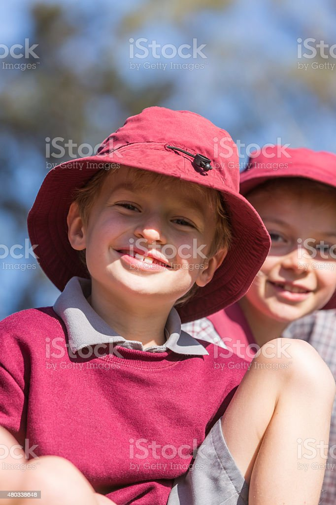 Happy School Boy in a Sunny Playground Wearing a Hat stock photo