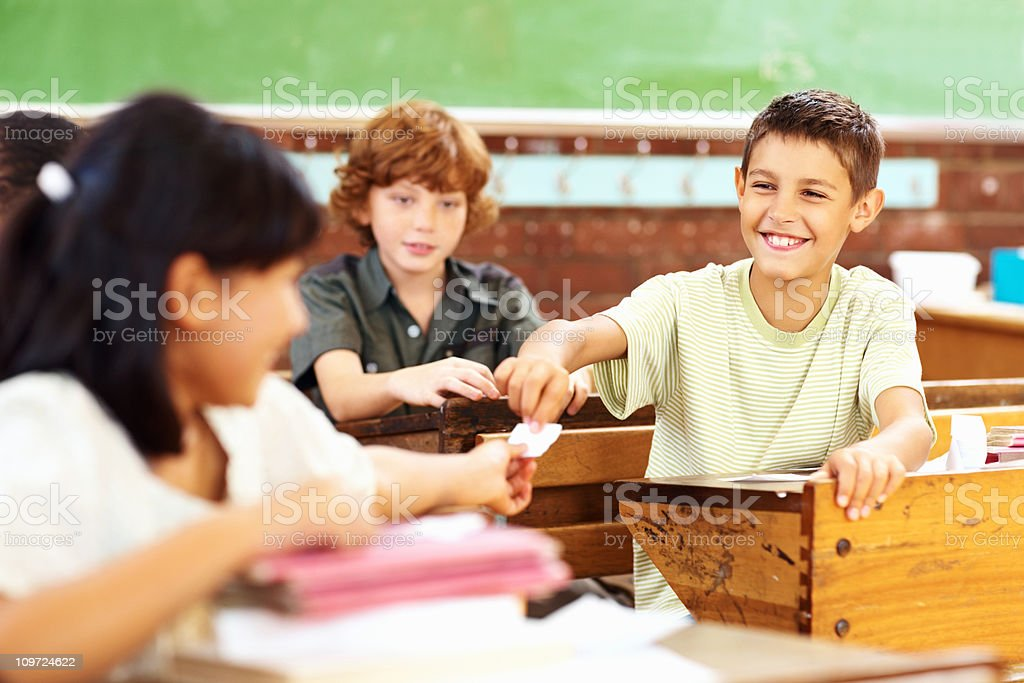 Happy school boy passing paper to a classmate royalty-free stock photo